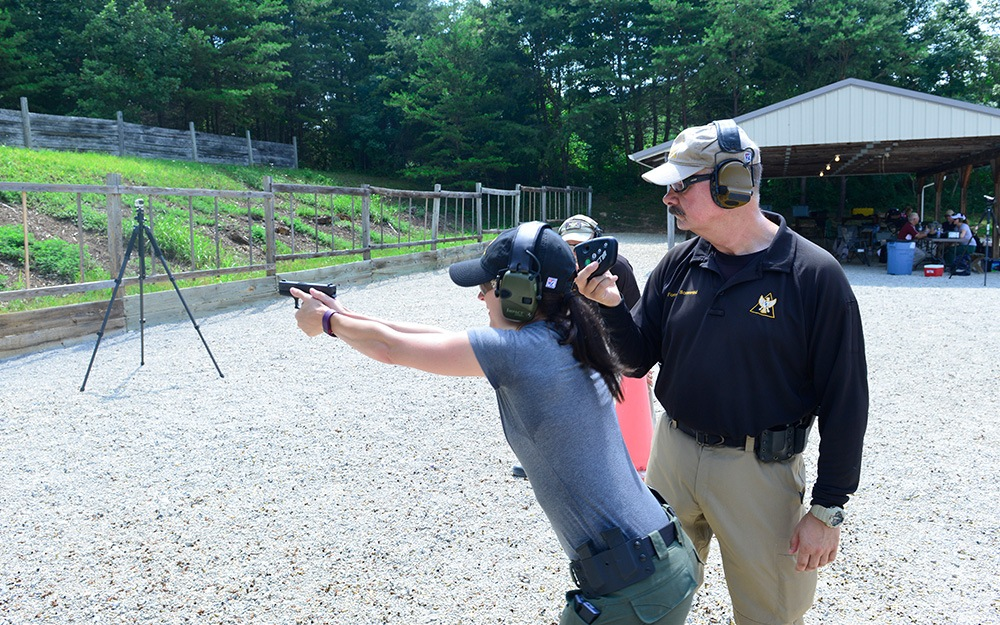 A veteran male training a middle-aged woman how to properly stand and aim her gun at a target.